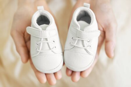 Tiny white baby shoes in man's hands. Closeup. Baby, pregnancy, parenting concept. 스톡 콘텐츠
