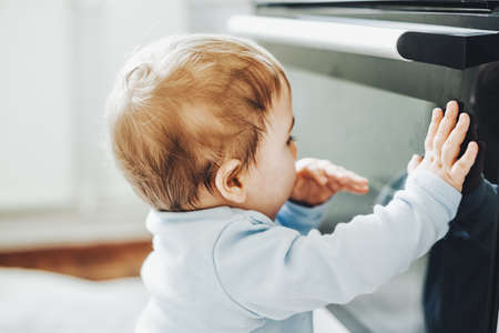Curious baby boy touching oven door in the kitchen. Baby or safety baby concept.