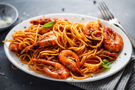 Pasta spaghetti with shrimps and tomato sauce served on plate on dark background. Closeup. Stockfoto