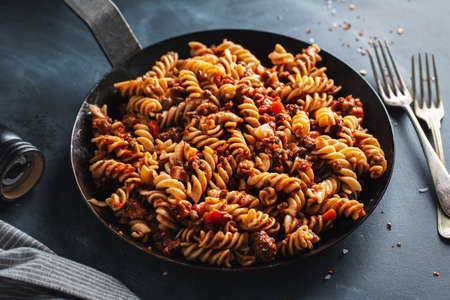 Classic italian pasta with minced meat and vegetables cooked and served on pan. Closeup. Stockfoto