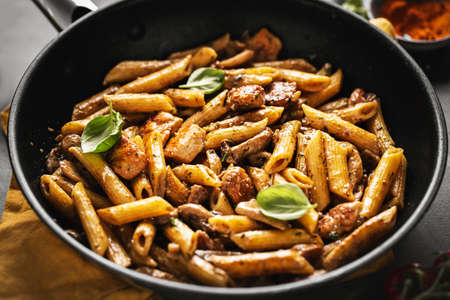 Tasty appetizing pasta penne with mushrooms in sauce. Served on pan. Stock Photo