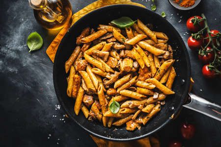 Tasty appetizing pasta penne with mushrooms in sauce. Served on pan. Stockfoto