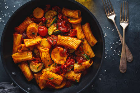 Tasty appetizing vegetarian pasta with vegetables and tomato sauce served on pan. Closeup. Stockfoto