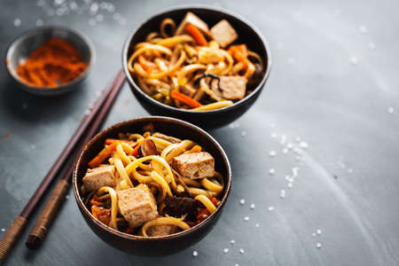 Tasty asian noodles with cheese tofu and vegetables in bowls. Stockfoto