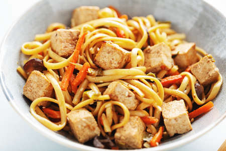 Tasty asian noodles with cheese tofu and vegetables on plate. Closeup. Stockfoto