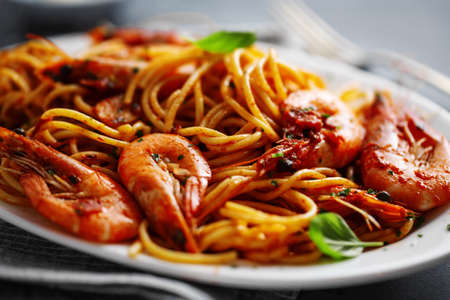 Pasta spaghetti with shrimps and tomato sauce served on plate on dark background. Stockfoto