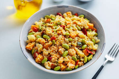 Quinoa with vegetables cooked for lunch or dinner and served in bowl. Closeup.