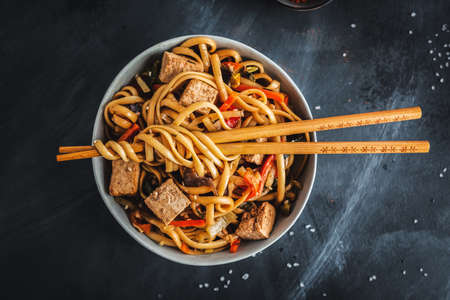 Tasty asian noodles with cheese tofu and vegetables on plate. Stockfoto