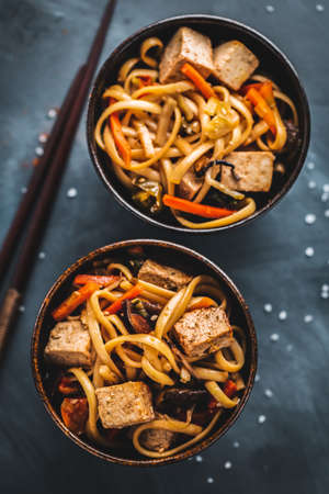 Tasty asian noodles with cheese tofu and vegetables on plates. Stockfoto