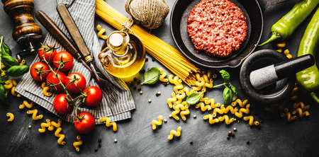 Italian food background with ingredients for cooking on dark background. View from above. Cooking concept.