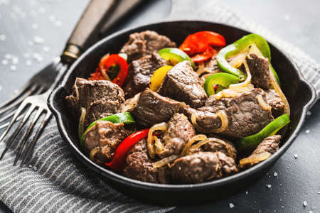 Closeup of tasty stuffed cooked cut beef or meat stew with paprika and onion served on skillet pan. Stockfoto