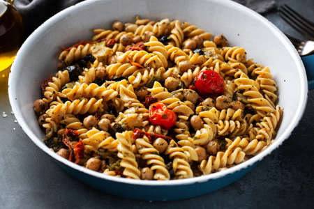 Tasty appetizing vegan pasta with vegetables and chickpeas cooked and served on pan. Closeup.