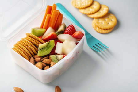 Lunch to go with fruits and vegetables in box. Closeup.