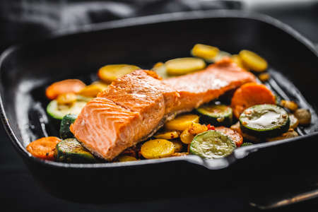 Tasty grilled salmon with vegetables served on grill pan.