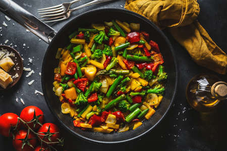 Fried vegetables in sauce cooked on pan. View from above. Vegan or vegetarian concept.