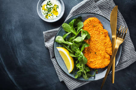 Classic german or austrian schnitzel with salad served on plate.