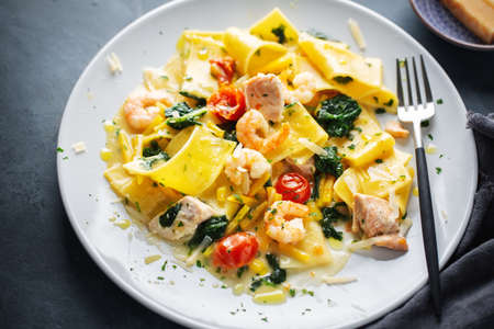 Tasty appetizing pasta with shrimps, vegetables and spinach served on plate. Closeup.