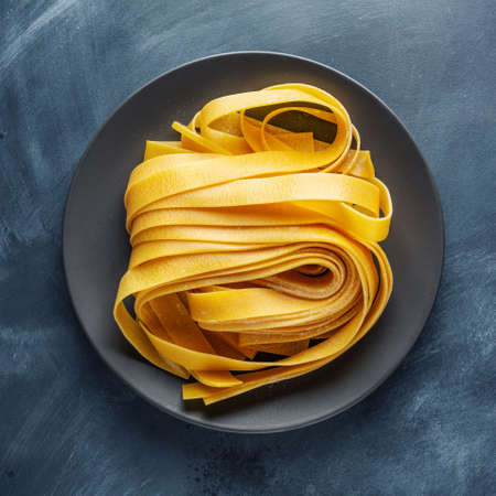Homemade pasta tagliatelle on plate on dark background. Food concept. Square.