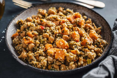 Warm salad with quinoa, chickpeas and sweet potato served on plate on dark background. Vegan or vegetarian food. Stockfoto