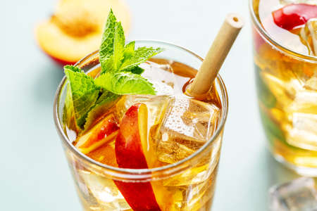 Tasty freshmade iced tea with peach, mint and ice cubes. Served in glasses with bamboo straw. Reklamní fotografie