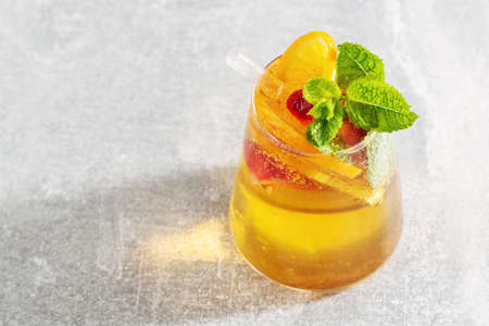 Tasty fresh drink with orange strawberry and mint served in glass. Closeup