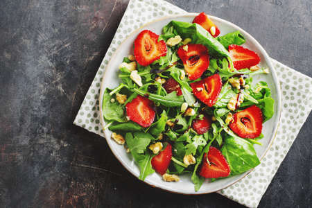 Tasty appetizing freshmade summer salad with arugula, strawberry and nuts served in bowl. Top view Reklamní fotografie
