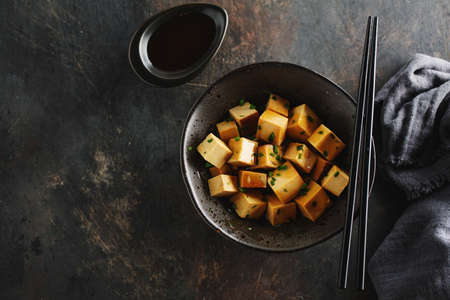 Tasty appetizing chunks of tofu with sauce served in bowl ready for eating. Closeup.