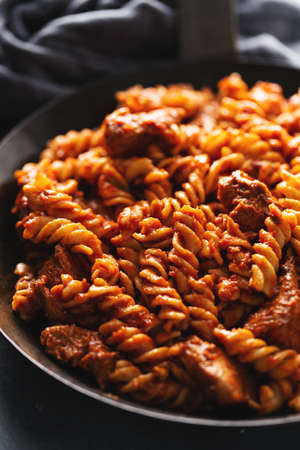 Tasty appetizing penne pasta with tomato sauce and meat served on pan. Closeup.