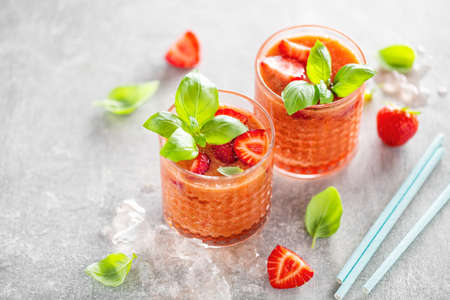 Tasty freshmade drink with stawberry and basil served in glasses on concrete background.