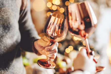 Closeup of people clink glasses. Christmas or New Year. Celebrating and toasting.