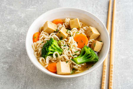 Tasty appetizing vegan asian soup with tofu, noodles and vegetables served in bowl on concrete background. Closeup.