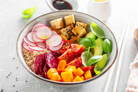 Tasty appetizing vegan bowl with vegetables and tofu served in bowl. Closeup.