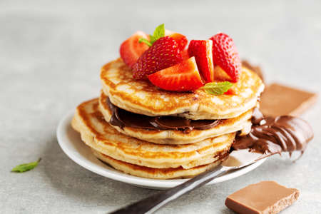 Tasty appetizing freshmade pancakes decorated with strawberry and chocolate paste served for breakfast. Closeup Reklamní fotografie