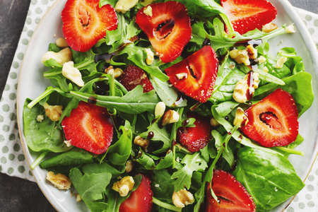Tasty appetizing freshmade summer salad with arugula, strawberry and nuts served in bowl. Closeup