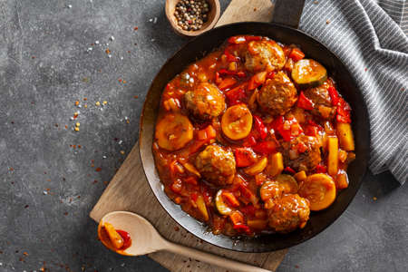Meatballs with vegetables and sauce made in pan and served on table.