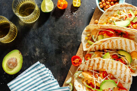 Tasty appetizing fresh homemade vegan tacos with chickpeas and vegetables served on board. Top view.
