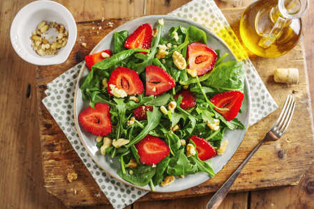 Tasty appetizing freshmade summer salad with arugula, strawberry and nuts served on plate. Closeup