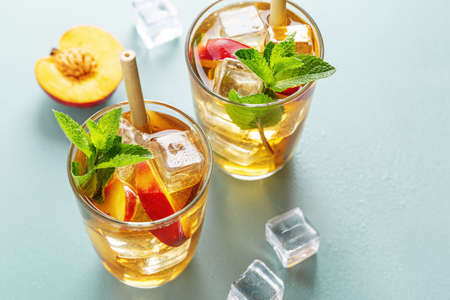 Tasty freshmade iced tea with peach, mint and ice cubes. Served in glasses with bamboo straw. Standard-Bild