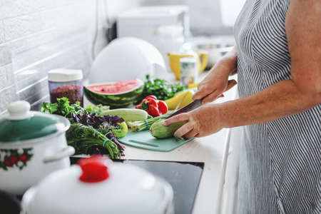 Woman cooking vegetables in the kitchen. Home cooking concept Standard-Bild