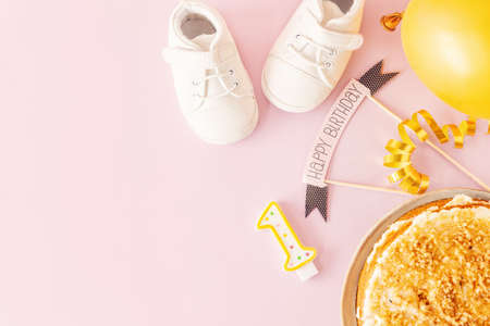 1st Birthday concept with baby accessories and birthday cake on pink background. Standard-Bild