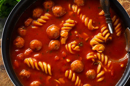 Italian tomato soup with noodles pasta and meatballs cooked in pan. Closeup Standard-Bild