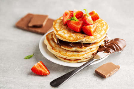 Tasty appetizing freshmade pancakes decorated with strawberry and chocolate paste served for breakfast. Closeup Standard-Bild