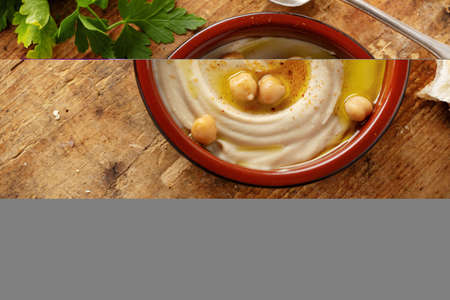 Freshmade oriental classic hummus served in bowl on the table. Closeup