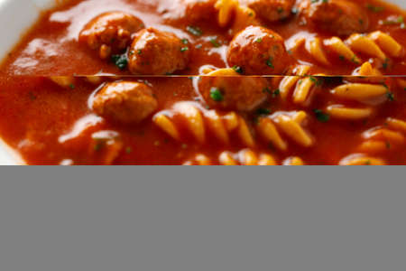 Italian tomato soup with noodles pasta and meatballs served on plate. Closeup Standard-Bild
