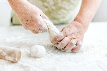 Woman at home kneading dough for cooking pasta pizza or bread. Home cooking concept. Lifestyle Standard-Bild