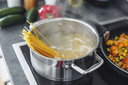 Boiling pot with cooking spaghetti pasta in the kitchen. Closeup Standard-Bild