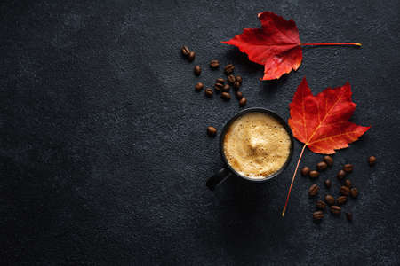 Autumn background with freshmade coffee in cup and maple leaves.