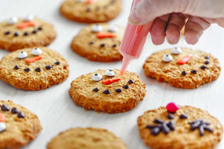 Woman decorates christmas cookies with snowman. Closeup