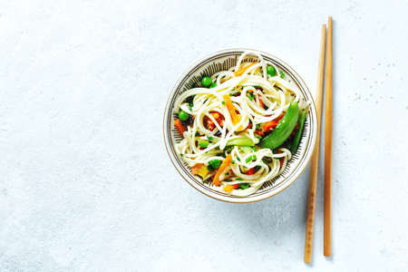 Asian noodles with vegetables and sesame served in bowl.