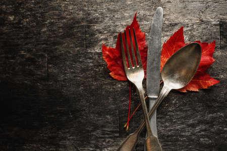 Vintage cutlery with autumn leaves on dark wooden backrground. Flat Lay. Autumn concept. Standard-Bild